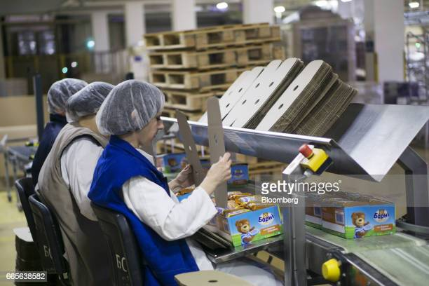 Workers box packets of Barni soft cakes at the end of the production line at the Trostyanets confectionery plant operated by Mondelez International...