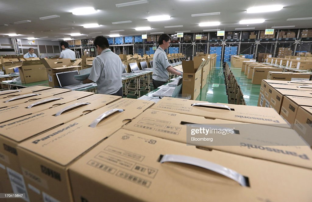 Workers box Panasonic Corp.'s Let's Note laptop computers after configuring software systems and programs at the company's plant in Kobe City, Hyogo Prefecture, Japan, on Tuesday, June 11, 2013. Panasonic manufactures electric and electronic products. Photographer: Yuriko Nakao/Bloomberg via Getty Images