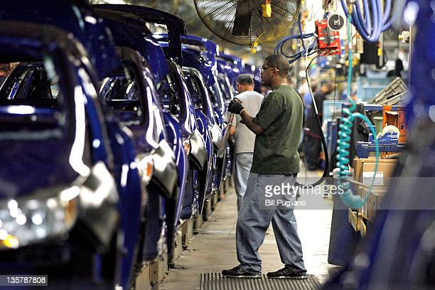 Workers build a Ford Focus on the assembly line at the Ford Motor Co's Michigan Assembly Plant December 14 2011 in Wayne Michigan Ford released...
