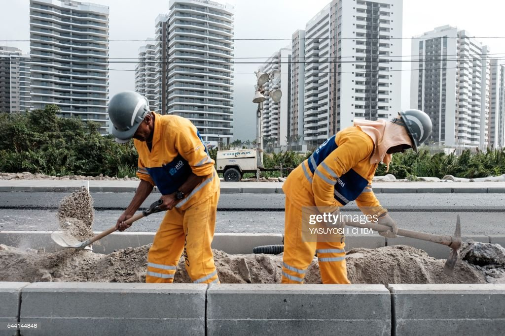 Workers build a new road called 'Transolimpica' that connect Barra da Tijuca and Deodoro, two major Olympic and Paralympic areas, including a special lane for the Bus Rapid Transit (BRT) near the Olympic and Paralympic Village in Rio de Janeiro, Brazil, on July 1, 2016. / AFP / YASUYOSHI