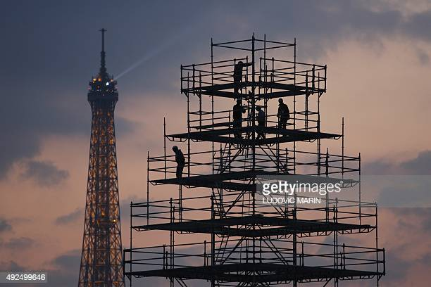 Workers build a scaffold on the Place de la Concorde near the Eiffel tower in Paris on October 13 2015 AFP PHOTO / LUDOVIC MARIN