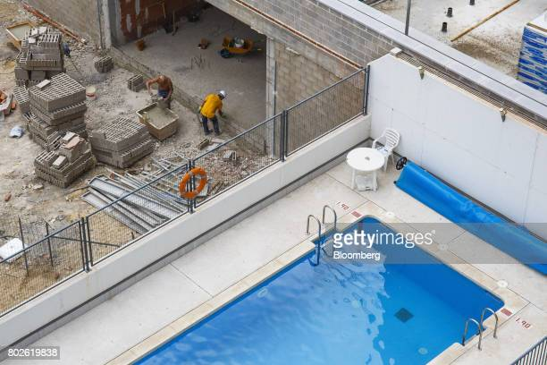 Workers build a wall at a construction site near a rooftop swimming pool in Madrid on Wednesday June 28 2017 Bankia SA agreed to acquire Banco Mare...