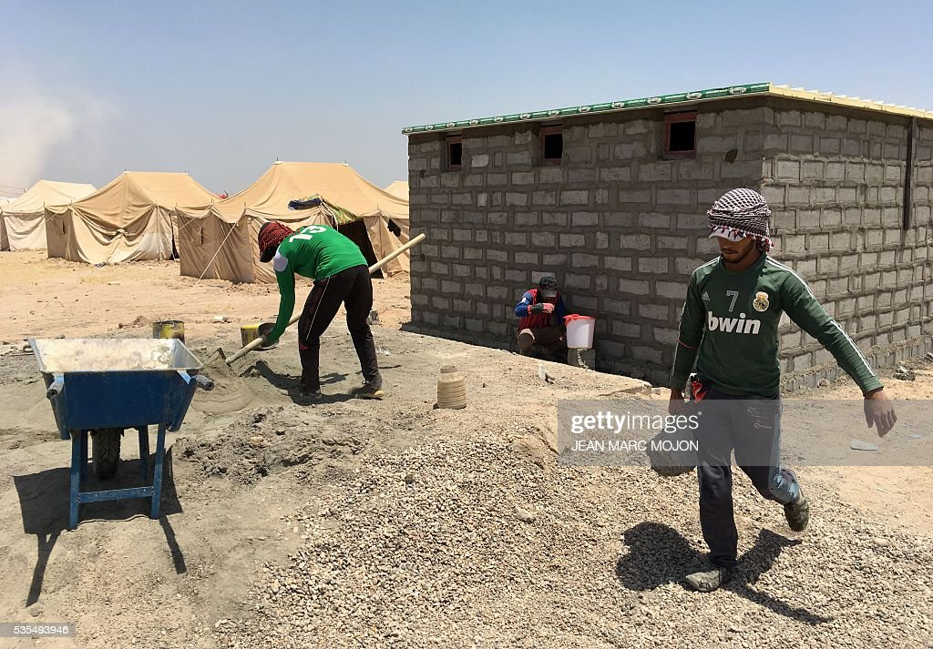 Workers build latrines on May 29, 2016 at a newly-opened camp in the government-held town of Amriyat al-Fallujah, 50 kilometres (30 miles) southwest of Baghdad, which was set up to shelter people fleeing violence around the city of Fallujah. The Norwegian Refugee Council, which runs the camp in Amriyat al-Fallujah, says around 3,000 people have managed to flee the area and reach displacement camps since Iraqi forces launched an operation against the Islamic State a week ago. The biggest wave of arrivals so far was Saturday night and included mostly exhausted and hungry women and children. / AFP / Jean Marc MOJON