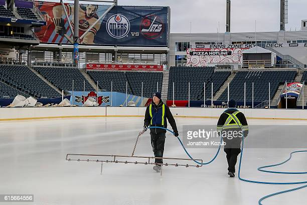 Workers build the ice prior to installing the lines and logos in advance of the 2016 Tim Hortons Heritage Classic on October 18 2016 at Investors...