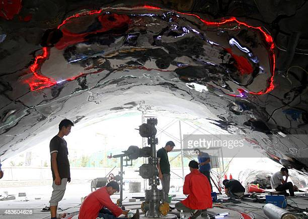 Workers build the oil bubbles sculpture at Well No1 on August 9 2015 in Karamay Xinjiang Uygur Autonomous Region of China Crude oil flow spurted out...