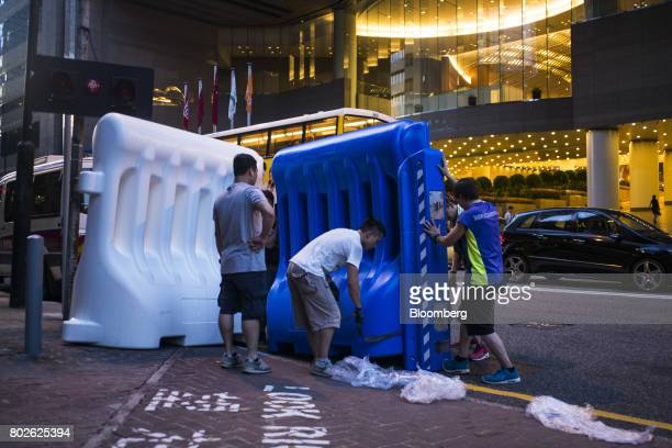 Workers build water barricades near the Hong Kong Convention and Exhibition Center ahead of Chinese President Xi Jinping's arrival in Hong Kong China...