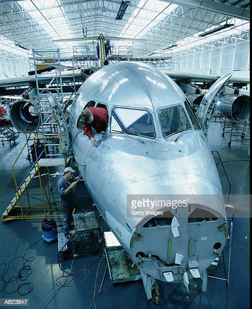 Workers building airplane in hanger