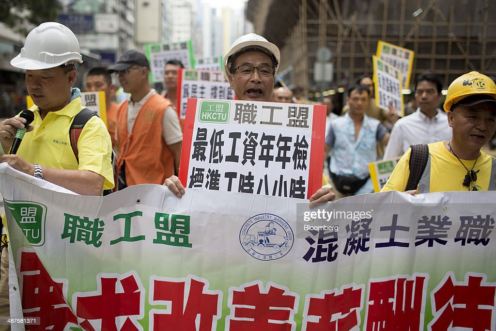 Workers carry a banner as they walk on a street during a labor day rally in Hong Kong, China, on Thursday, May 1, 2014. Thousands of people have marked labor day by staging a series of rallies to demand better workers' rights. Photographer: Brent Lewin/Bloomberg via Getty Images