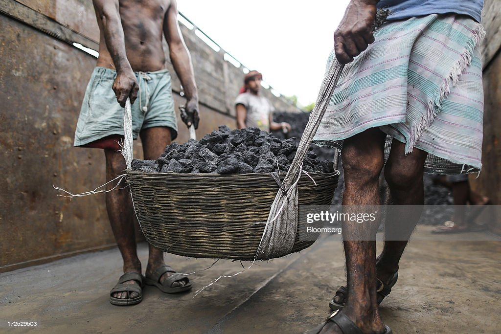 Workers carry a basket of coal during the unloading of a truck at a coal wholesale market in Mumbai, India, on Tuesday, July 2, 2013. India, the worlds third-largest coal consumer, imported 43 percent more of the fuel than a year ago on increased demand from power stations and steelmakers, according to shipping data, and is set to eclipse China as the top importer of power station coal by 2014. Photographer: Dhiraj Singh/Bloomberg via Getty Images