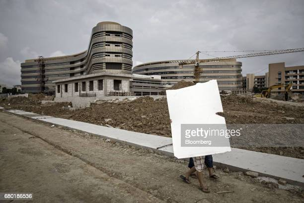 Workers carry a styrofoam board past the construction site of the Evergrande International Hospital inside the Hainan Boao Lecheng...