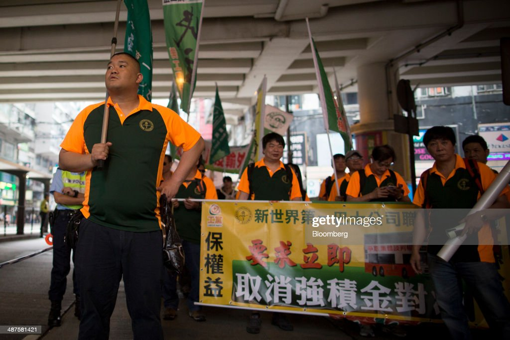 Workers carry banners and signs as they walk on a street during a labor day rally in Hong Kong, China, on Thursday, May 1, 2014. Thousands of people have marked labor day by staging a series of rallies to demand better workers' rights. Photographer: Brent Lewin/Bloomberg via Getty Images