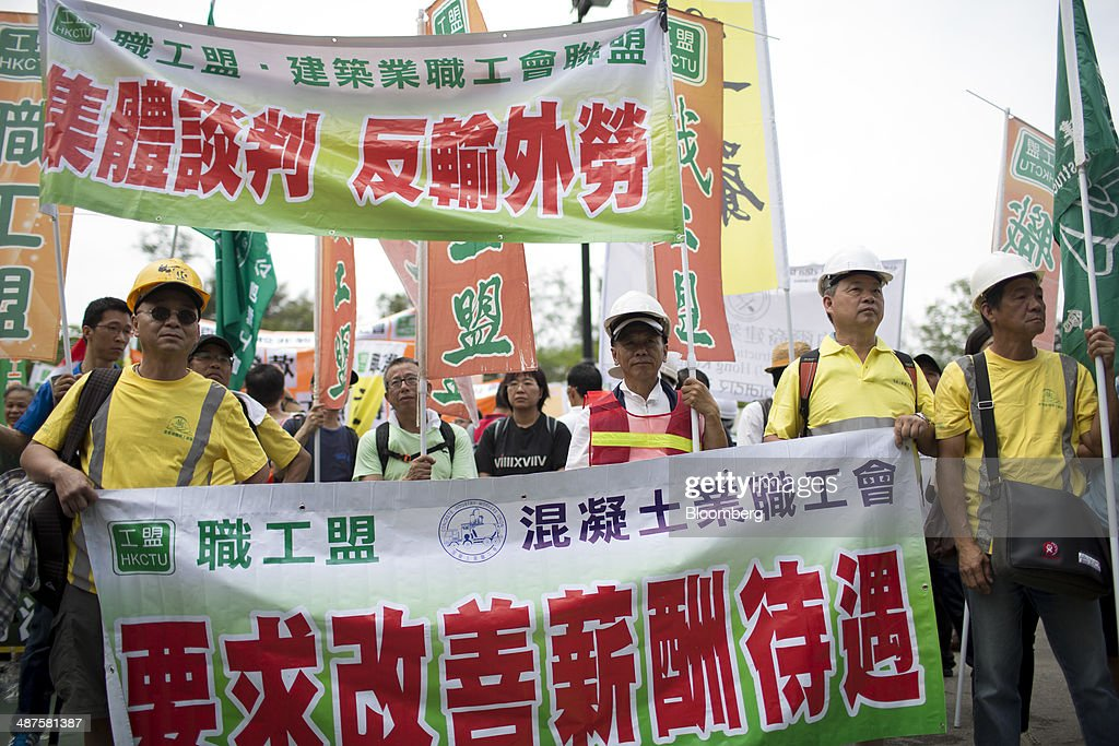 Workers carry banners and signs at Victoria Park during a labor day rally in Hong Kong, China, on Thursday, May 1, 2014. Thousands of people have marked labor day by staging a series of rallies to demand better workers' rights. Photographer: Brent Lewin/Bloomberg via Getty Images