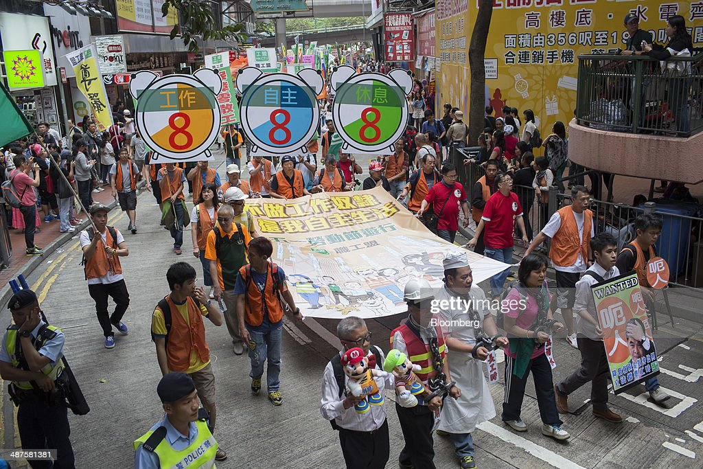 Workers carry banners, signs and placards as they walk on a street during a labor day rally in Hong Kong, China, on Thursday, May 1, 2014. Thousands of people have marked labor day by staging a series of rallies to demand better workers' rights. Photographer: Brent Lewin/Bloomberg via Getty Images