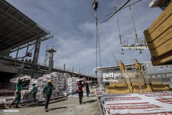 Workers carry building materials during construction of Terminals 3 and 4 at the Sao Paulo/Guarulhos Governor Andre Franco Montoro International...