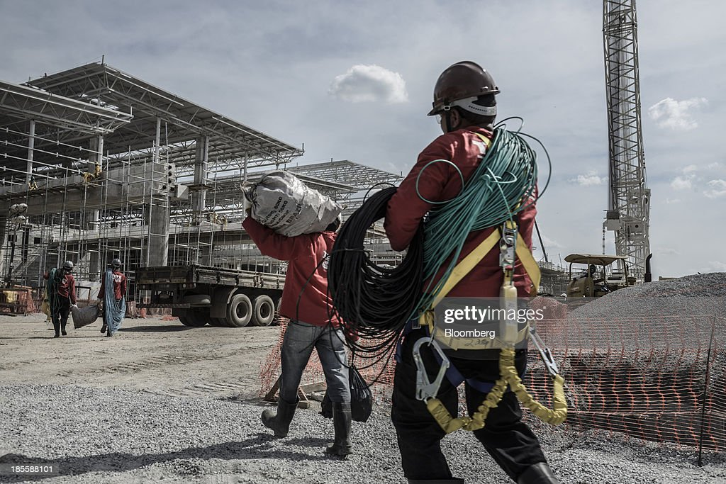 Workers carry construction materials during an expansion project at the Sao Paulo/Guarulhos Governor Andre Franco Montoro International Airport in...