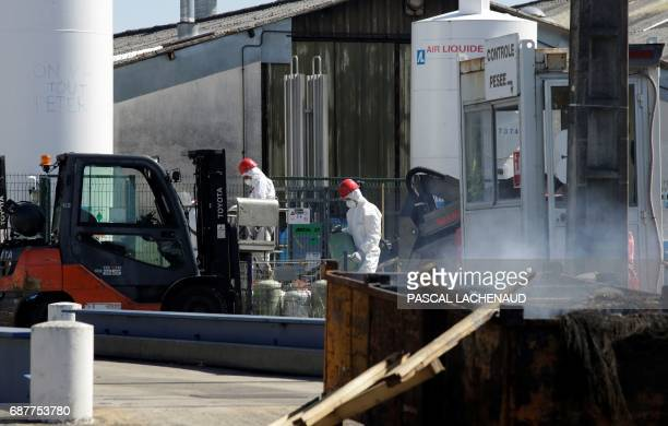 Workers carry gas cylinders after they took them off an Air Liquide gas holder at the site of ailing car parts factory GmS Industry factory in La...