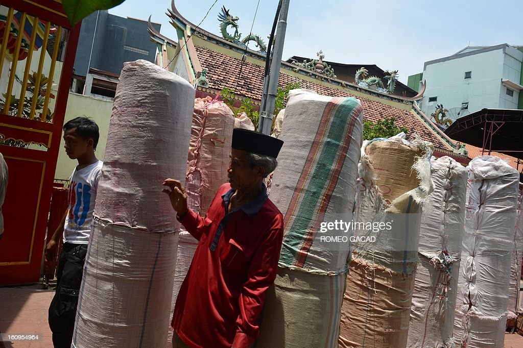 Workers carry giant candles to a Buddhist temple in the Indonesian capital city of Jakarta on February 8, 2013 as the Muslim majority country's minority Chinese-Indonesians prepares to celebrate the Chinese Lunar New Year. The 'Year of the Snake' falls across the region on February 10, 2013.