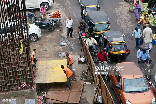 Workers carry materials at a construction site as traffic moves along a road in Patna Bihar India on Friday July 10 2015 Anyone placing bets on...