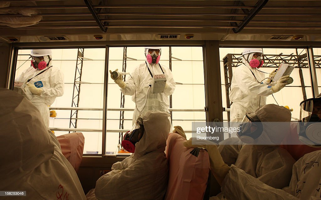 Workers carry out radiation screening on a bus for a media tour at Tokyo Electric Power Co.'s (Tepco) Fukushima Dai-Ichi nuclear power plant in Okuma Town, Fukushima Prefecture, Japan, on Saturday, May 26, 2012. Japan, once the world's largest user of nuclear power after the U.S. and France, has all of its 50 reactors offline as the country runs safety tests following the Fukushima atomic disaster. Photographer: Tomohiro Ohsumi/Bloomberg via Getty Images