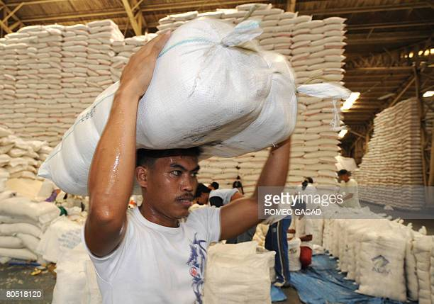Workers carry repacked imported rice from the US and Vietnam at the government National Food Authority grains warehouse in Manila on April 4 2008 for...