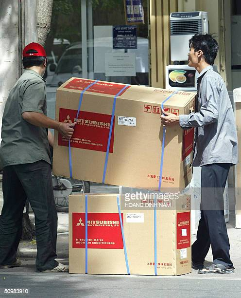 Workers carry room air conditioners in front of an electrical appliance shop in downtown Hanoi 22 June 2004 A wave of heat has been sweeping Northern...