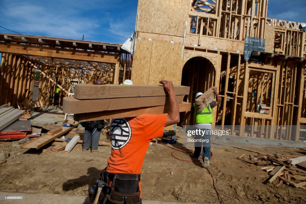 Workers carry stacks of lumber into a house under construction at Davidson Communities LLC's Arista at The Crosby development in Rancho Santa Fe, California, U.S., on Friday, Dec. 21, 2012. New home sales climbed to a 380,000 annual rate in November, the most since April 2010, according to the median forecast of 60 economists surveyed by Bloomberg before Dec. 27 figures from the Commerce Department. Photographer: Sam Hodgson/Bloomberg via Getty Images