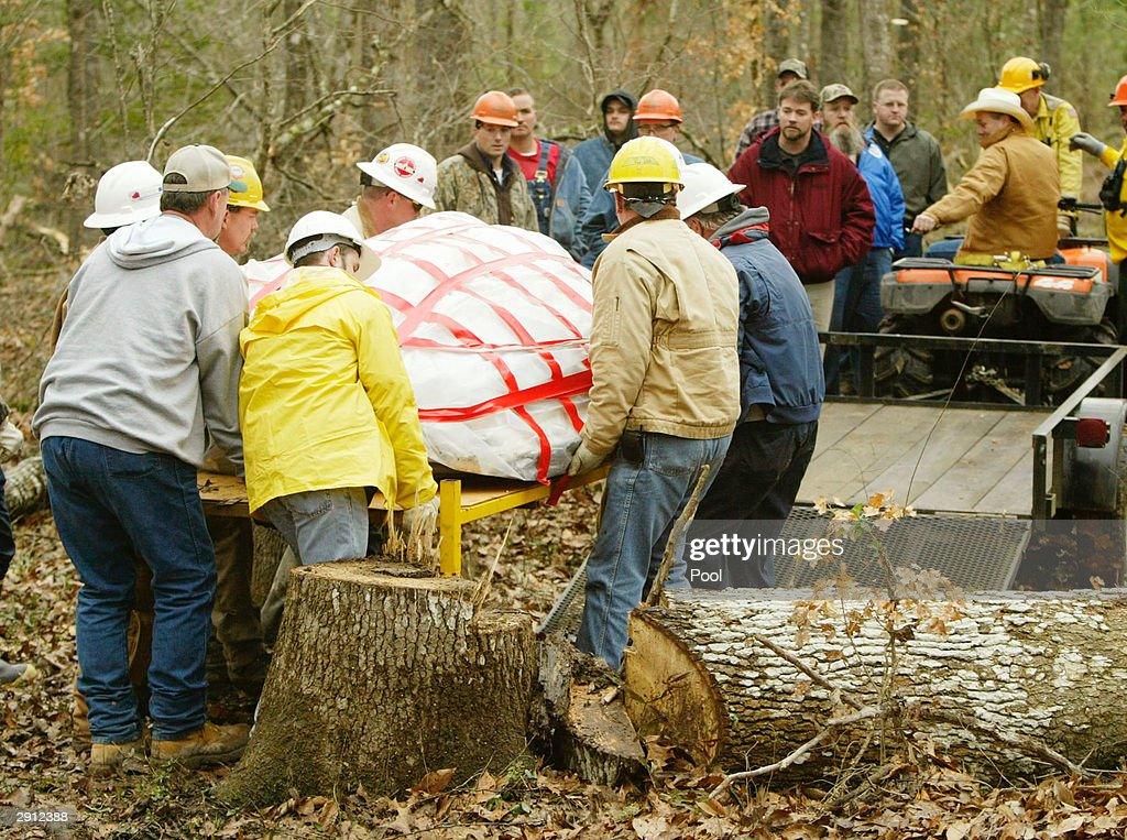 Workers carry the nose cone of the space shuttle Columbia out of the woods to load it onto a trailer February 5, 2003 near Hemphill, Texas. The one-year anniversary of the space shuttle Columbia disaster during reentry will be marked February 1, 2004.