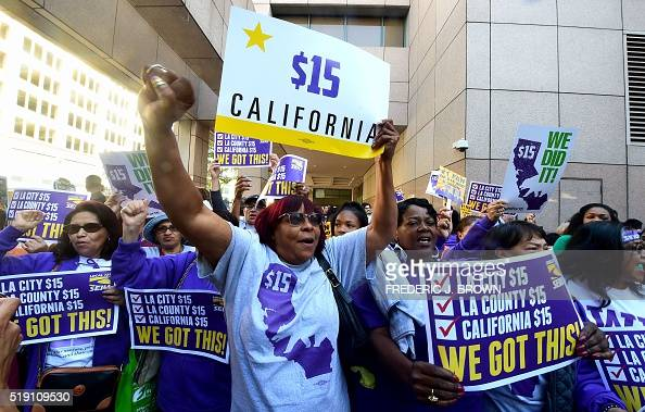 Workers celebrate outside the Ronald Reagan State Building in downtown Los Angeles where California Governor Jerry Brown signed the bill that will...