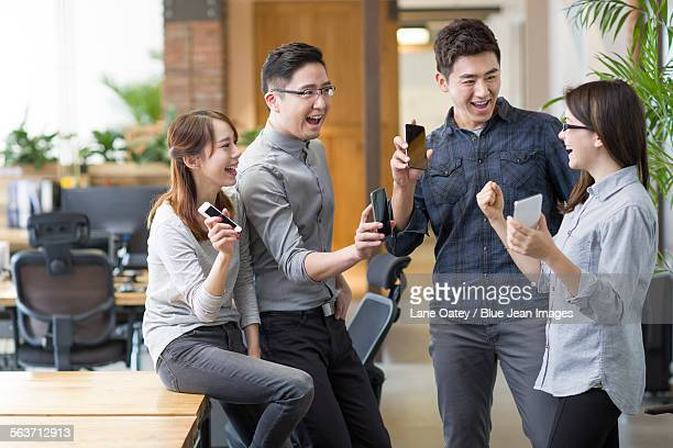 IT workers celebrating with smart phones in office