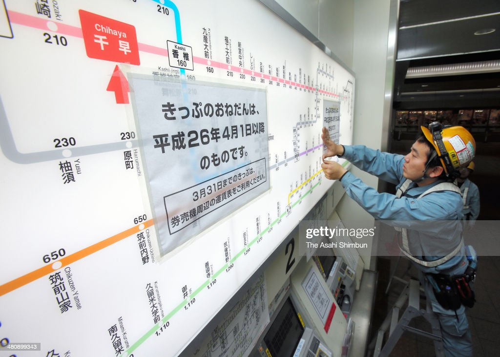 Workers change to the new tariff above the ticket vending machines as a preparation of the three percent consumption tax hike starting on April 1, at JR Chihaya Station on March 27, 2014 in Fukuoka, Japan. Japan raises consumption tax from 5 to 8 percent on April 1, and possibly to 10 percent in October 2015, despite market concerns about a slowing of the economic recovery.