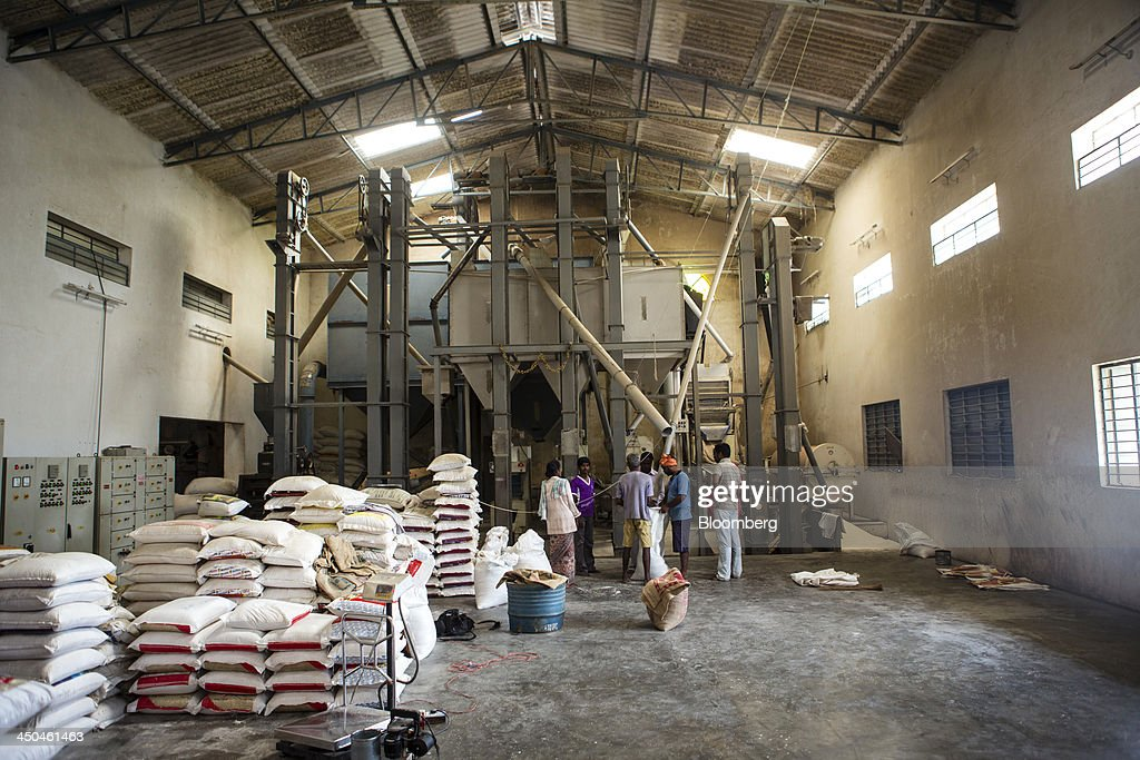 Workers chat as they fill bags of rice beside the polishing machine at the KRK Modern Rice Mill in Kothapeta, Tamil Nadu, India, on Thursday, Nov. 14, 2013. Record onion prices and the soaring cost of rice and coriander are frustrating Reserve Bank of India Governor Raghuram Rajans battle to curb inflation while supporting growth in Asias third-largest economy. Photographer: Prashanth Vishwanathan/Bloomberg via Getty Images