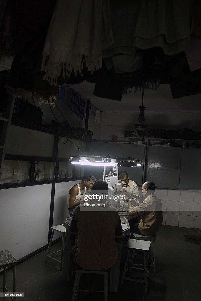Workers check and polish diamonds inside a diamond cutting and polishing workshop in Mumbai, India, on Monday, Sept. 17, 2012. Sales of diamond jewelry in India are set to rise 16 percent annually in the five years to 2015, twice as fast as the 7 percent growth predicted for adornments made of the yellow metal, according to a study by New Delhi-based consultants AM Mindpower Solutions. Photographer: Adeel Halim/Bloomberg via Getty Images