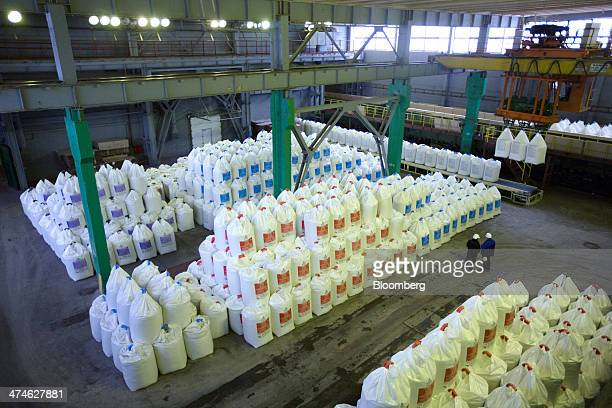 Workers check bags of fertilizer as they sit in a warehouse awaiting shipment from the OAO Phosagro plant in Cherepovets Russia on Friday Feb 21 2014...