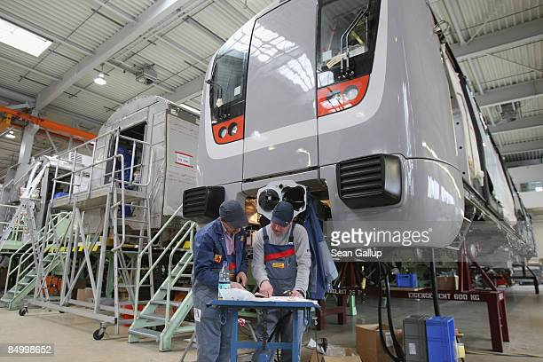 Workers check blueprints for a subway car destined for New Delhi India at the train factory of Canadian company Bombardier on February 23 2009 in...