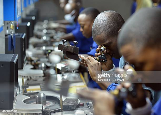 Workers check cut and polish diamonds at a Diamond cutting and polishing company during the tour by Ghanian President John Dramani Mahama in Gaborone...