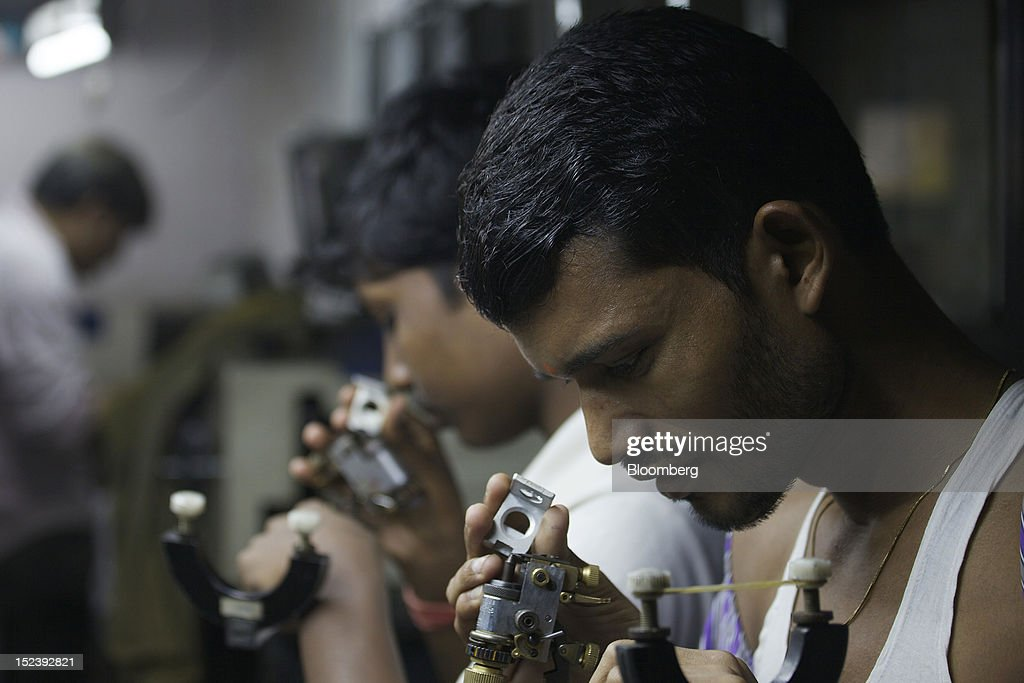 Workers check diamonds inside a diamond cutting and polishing workshop in Mumbai, India, on Monday, Sept. 17, 2012. Sales of diamond jewelry in India are set to rise 16 percent annually in the five years to 2015, twice as fast as the 7 percent growth predicted for adornments made of the yellow metal, according to a study by New Delhi-based consultants AM Mindpower Solutions. Photographer: Adeel Halim/Bloomberg via Getty Images