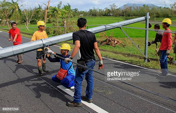 Workers check downed electric posts on the national road after typhoon NockTen made landfall in Nabua Camarines Sur on December 26 2016 Typhoon...