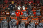 Workers check machines they produce in a machinery and equipment manufacturing factory in Huaibei east China's Anhui province on September 17 2013...