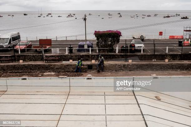 Workers check on water pumps as they work on the rehabilitation of a public pool on the forshore of Jamestown on October 18 2017 in the British...