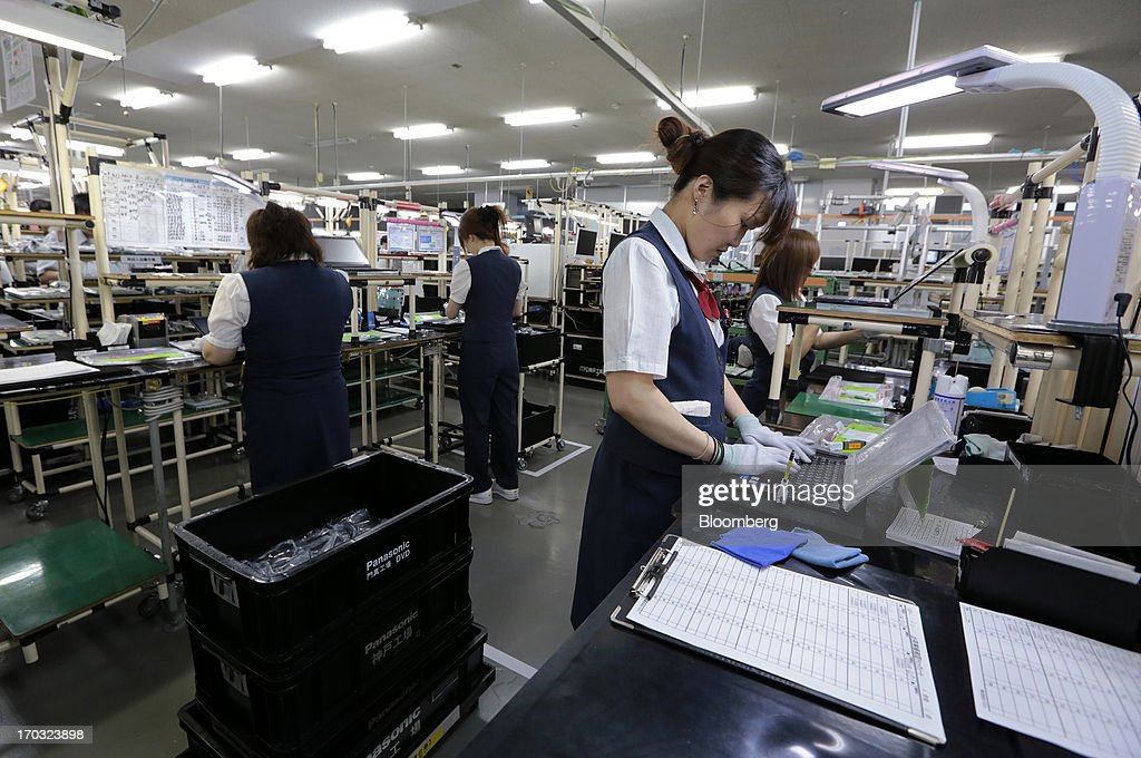 Workers check Panasonic Corp.'s laptop computers on the production line at the company's plant in Kobe City, Hyogo Prefecture, Japan, on Tuesday, June 11, 2013. Panasonic manufactures electric and electronic products. Photographer: Yuriko Nakao/Bloomberg via Getty Images