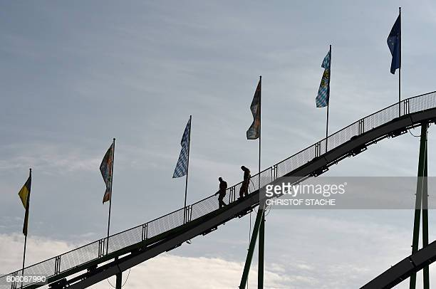 Workers check the roller coaster track pior to the opening of the Oktoberfest beer festival at the Theresienwiese fair grounds in Munich southern...