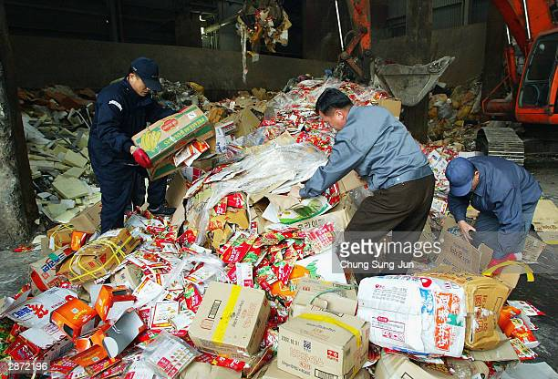 Workers check through products made from US imported beef in front of trash burner on January 16 2004 in Incheon South Korea A South Korean food...