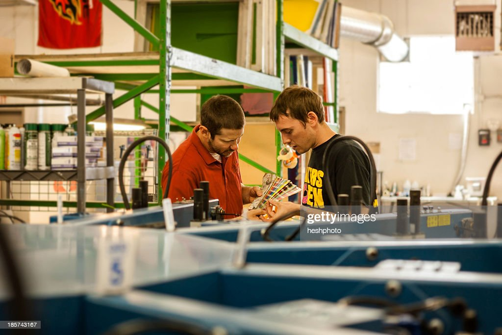 Workers checking color swatches in screen print workshop : Stock Photo