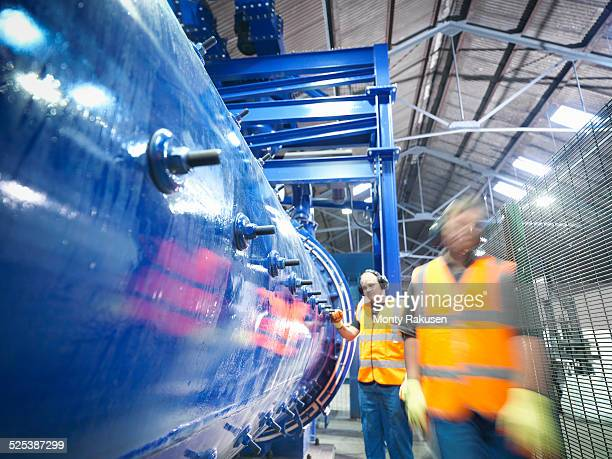 Workers checking metal ore grinding mill