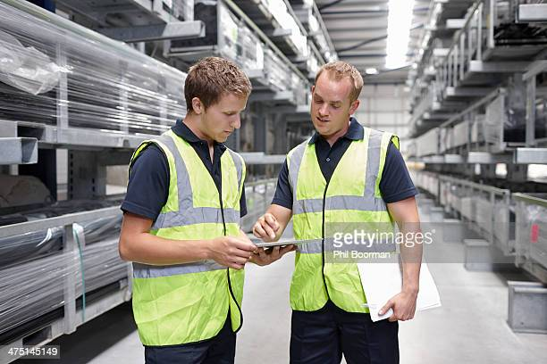 Workers checking orders in engineering warehouse