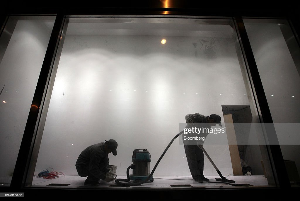 Workers clean a show window at night in Shanghai, China, on Monday, Jan. 28, 2013. China's economic growth accelerated for the first time in two years as government efforts to revive demand drove a rebound in industrial output, retail sales and the housing market. Photographer: Tomohiro Ohsumi/Bloomberg via Getty Images