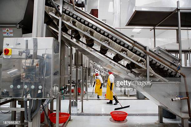 Workers clean equipment as chili peppers are washed before being ground up for Sriracha hot sauce at the Huy Fong Foods Inc facility in Irwindale...