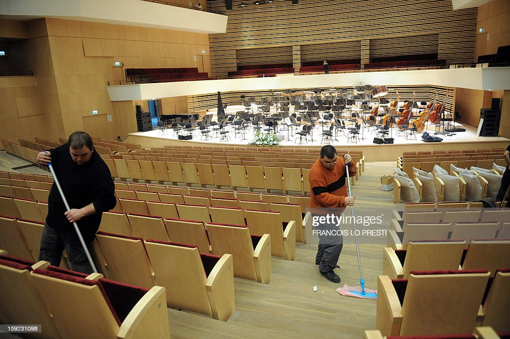 Workers clean on January 10, 2013 the 'Nouveau Siecle' (New Century) auditorium in Lille ahead of a performance tonight by French conductor Jean-Claude Casadesus and the Lille National Orchestra to mark its reopening after a complete renovation.
