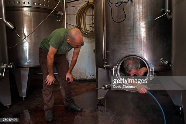 Workers clean stainless steel vats for the 2007 cabernet sauvignon production October 16 2007 at the Margalit boutique winery near Hadera in central...