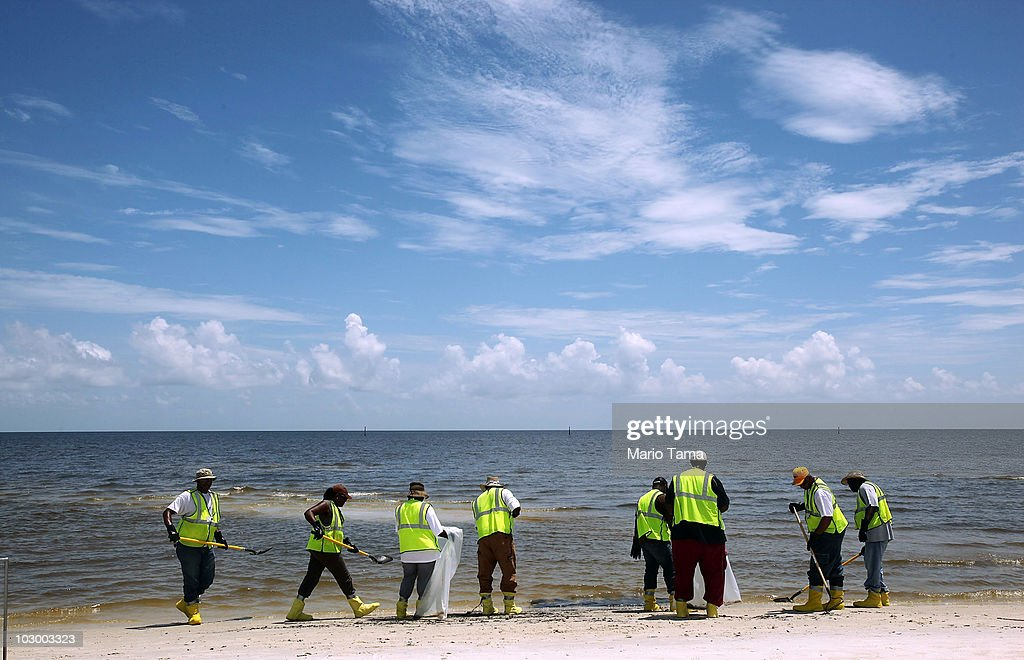 Workers clean tarballs from a beach July 20, 2010 in Pass Christian, Mississippi. Scientists are concerned that the leaking BP well cap is possibly an indication that the oil well is buckling.